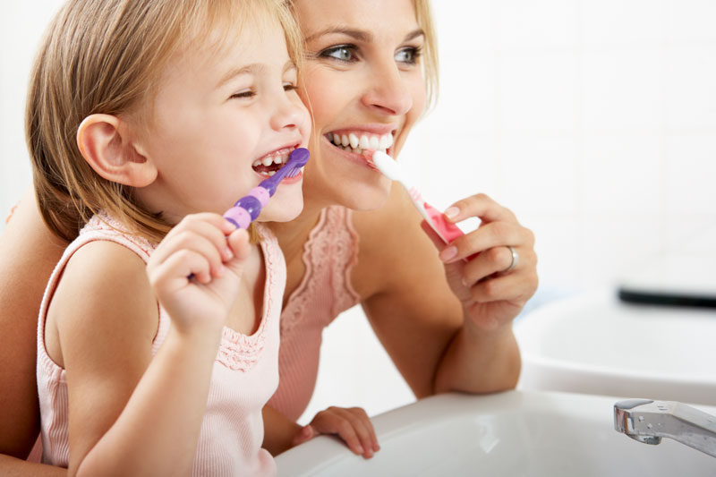Oral Hygiene - Mother and Daughter Brushing Their Teeth